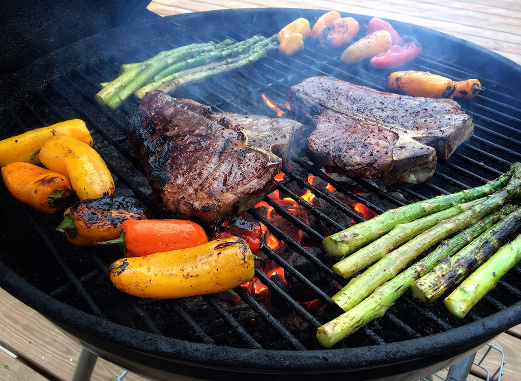 Grilling veggies and steak on grill