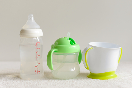 Three kinds of bottles and cups with water for baby