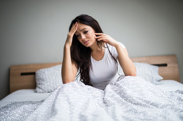 woman feel sick and unwell on bed
