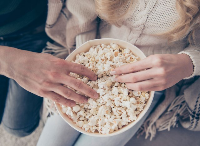man and woman eating popcorn