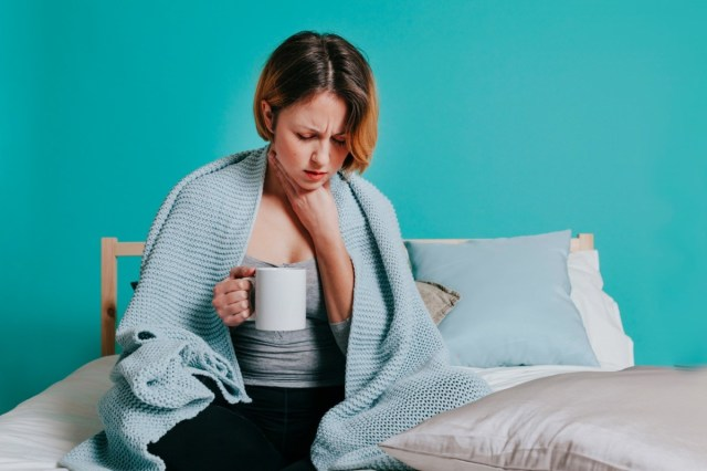Woman sore throat with glass of water in her bed