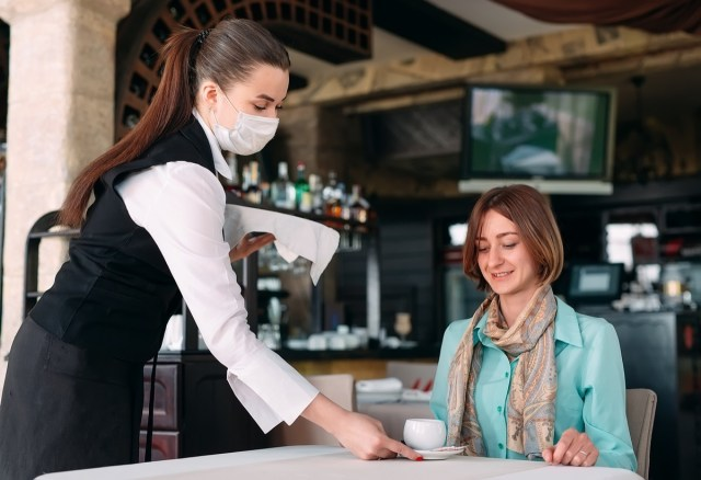waiter in a medical mask serves coffee