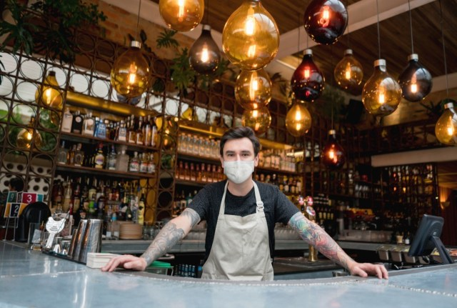 Happy bartender working at a bar wearing a face mask.