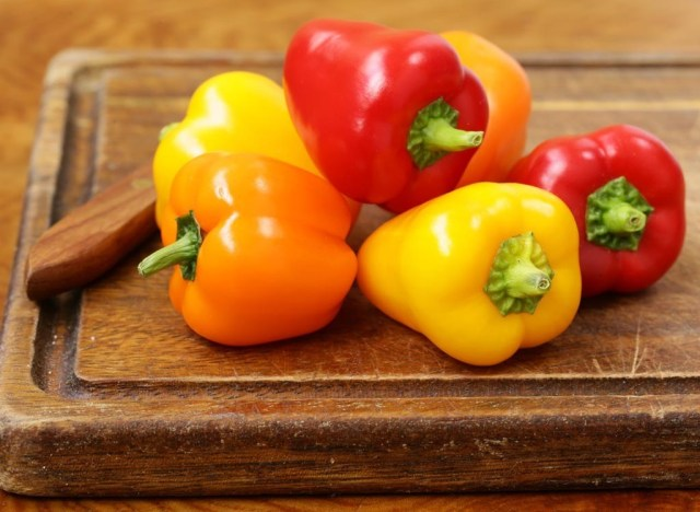 orange yellow and red bell peppers on wood cutting board