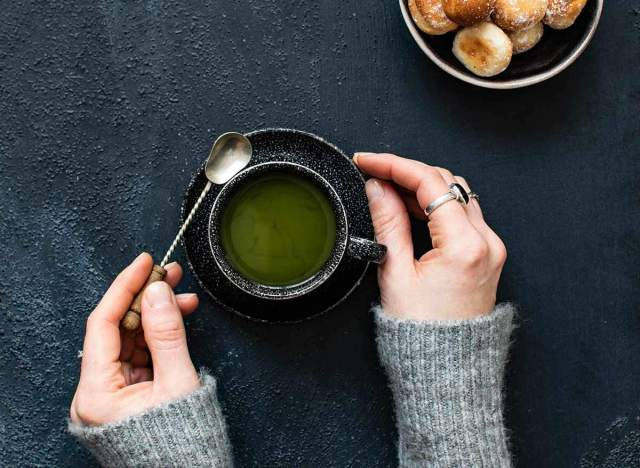 holding a cup of green tea