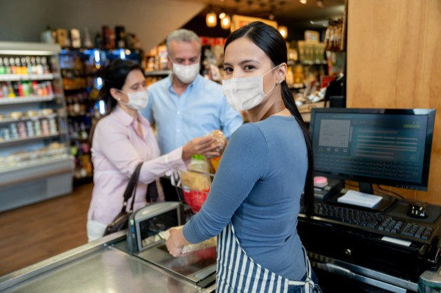 Cashier working at the supermarket wearing a facemask while scanning products