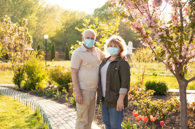 Elderly couple embracing in spring or summer park wearing medical mask to protect from coronavirus