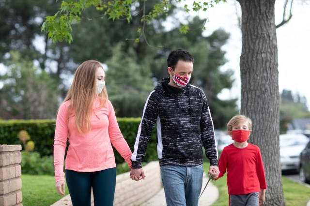 A family walking holding hands wearing face masks in the middle of pandemic
