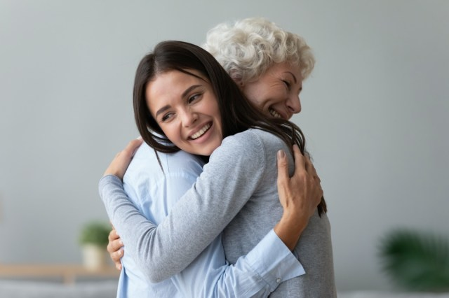 Happy young lady adult daughter granddaughter visiting embracing hugging old senior retired grandmother cuddling
