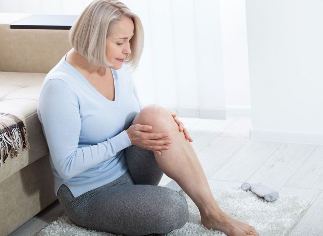 Woman holding leg in pain