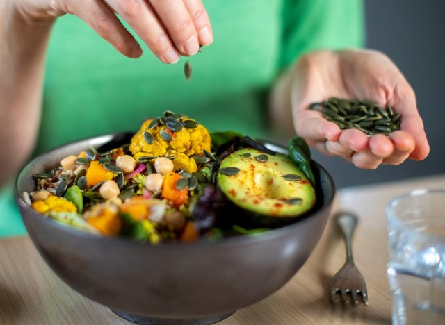 woman adding pumpkin seeds to a salad bowl vegetables avocado plant based meal