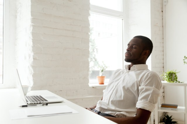 man relaxing after work breathing fresh air sitting at home office desk with laptop