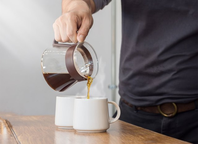 coffee pot pouring into two mugs