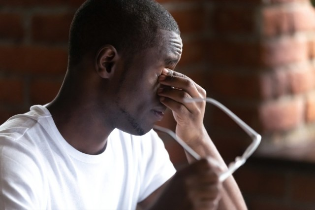 Close up black african man taking off glasses feels unhealthy suffering from eye strain after long working on computer