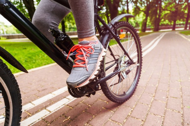 cyclist woman feet riding mountain bike on trail