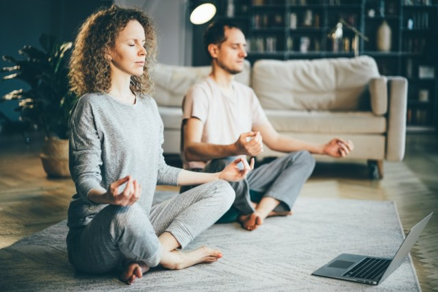 Calm couple in pajamas meditating, listening spiritual practices lessons on laptop, sitting on lotus pose at home