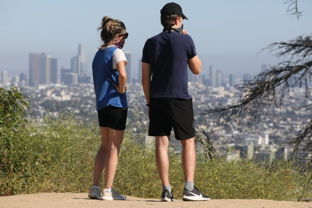 couple wearing masks due to corona virus pandemic at the Griffith Park in Los Angeles
