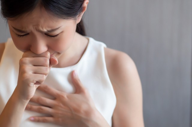 Sick woman coughing, experiencing hiccup.