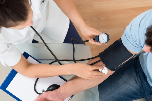 Doctor Checking Blood Pressure Of Male Patient