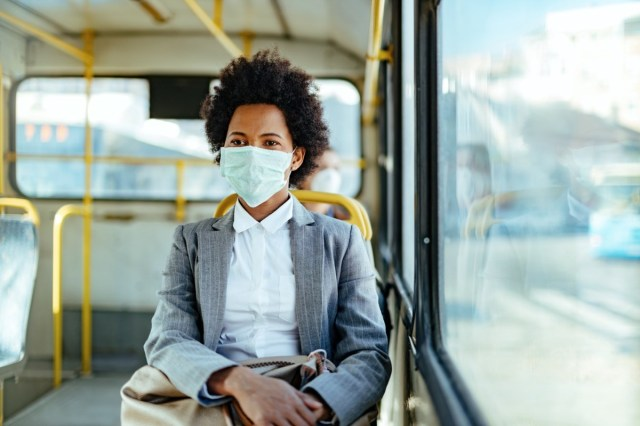 sinesswoman wearing protective mask while traveling by public transportation.