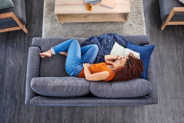 Woman suffering from stomach cramps on the sofa at home.