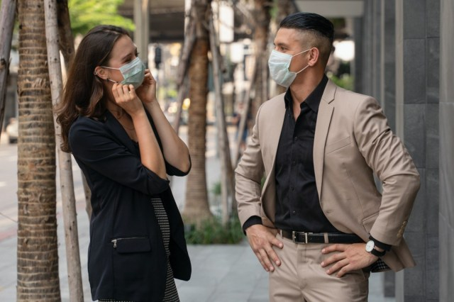 people wearing medical mask for coronavirus covid 19 protection standing together beside office building and talking in city