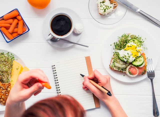 Woman writing in food journal with egg toast carrots coffee on table