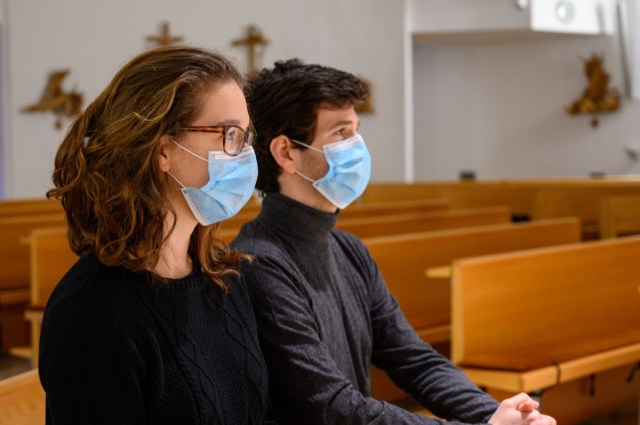 A young couple in face masks praying in a church during the COVID-19 pandemic.
