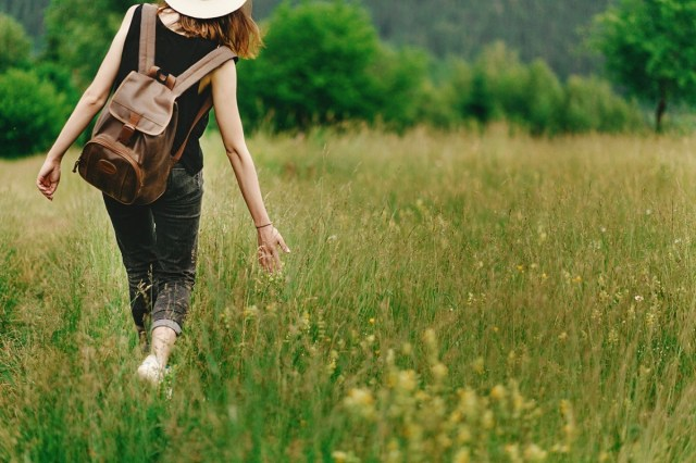 woman walking in grass and holding in hand herb wildflowers