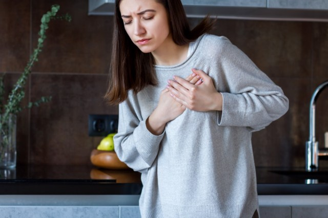 Woman in grey clothes is holding hands on her chest.
