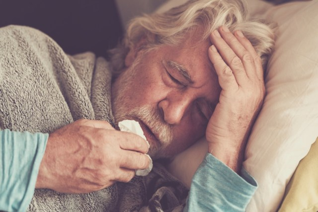 senior man with winter seasonal illness fever cold problems