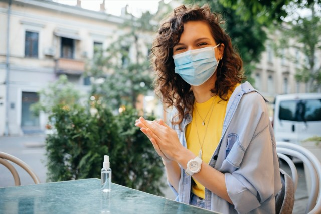 Happy young woman wearing protective face mask disinfects her hands with alcohol sanitizer while sitting at table in restaurant on summer day.