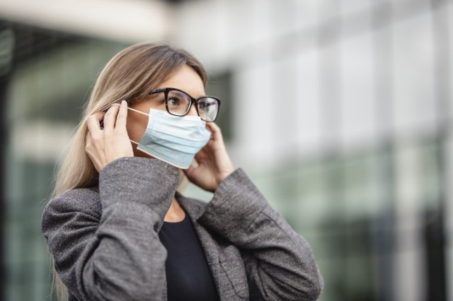 Woman put on medical protective mask for protection against coronavirus.