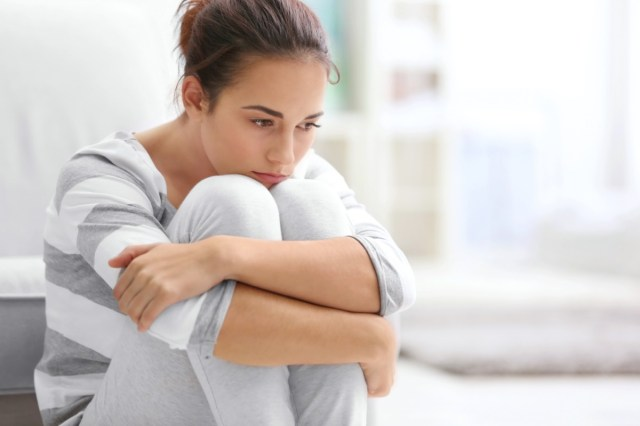Depressed young woman sitting on floor at home