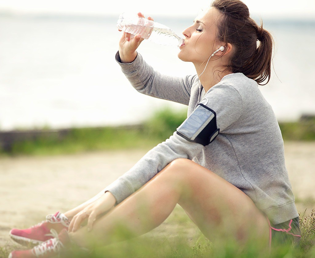 Woman drinking water after run