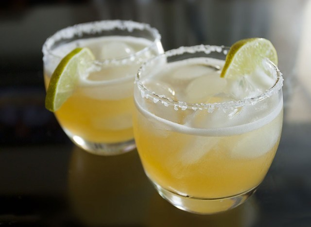 two margaritas in glasses with lime wedges