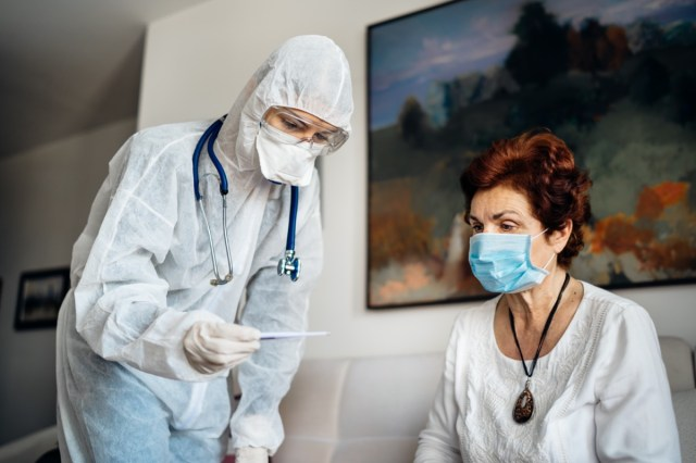Home care doctor wearing personal protective equipment(PPE).Infection and cross-contamination during home visit to suspect COVID-19 senior patient