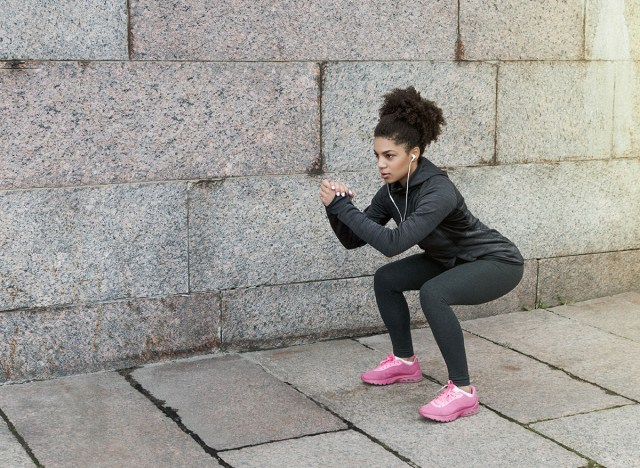 woman doing squats outside