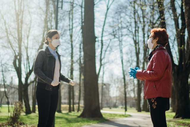 Elderly woman with protective face mask/gloves talking with a friend