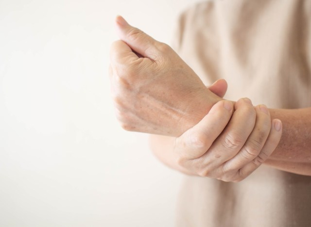 senior woman holding wrist with joint pain poor bone health
