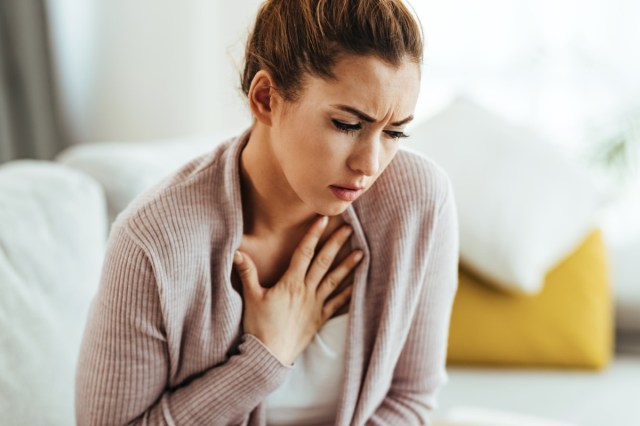 Young woman feeling sick and holding her chest in pain at home.