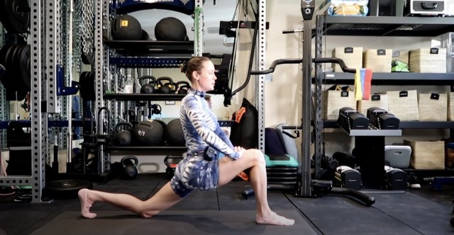 brie larson doing a lunge in blue workout clothes
