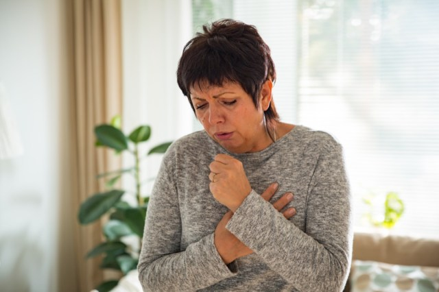 Mature woman with sore throat, standing in living room at home.