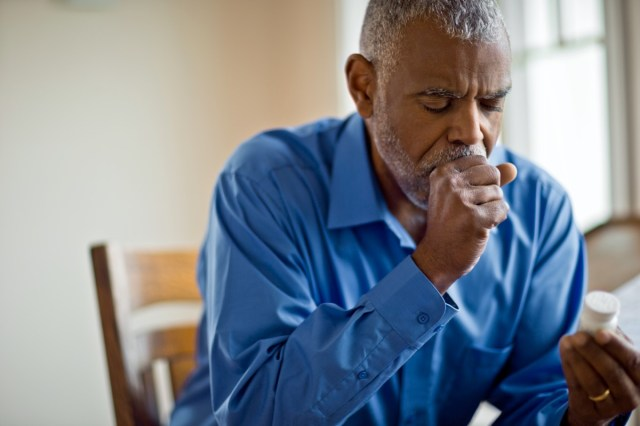 Sick man looks at pill bottle whilst coughing.