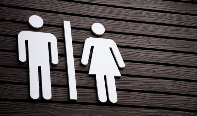 Restroom sign on a toilet door,on wood background