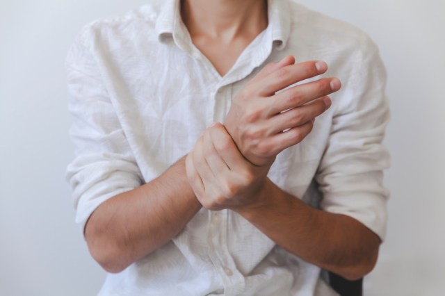 male arms holding his painful wrist