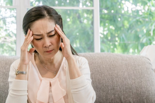 Asian woman sitting on the sofa and having an headache