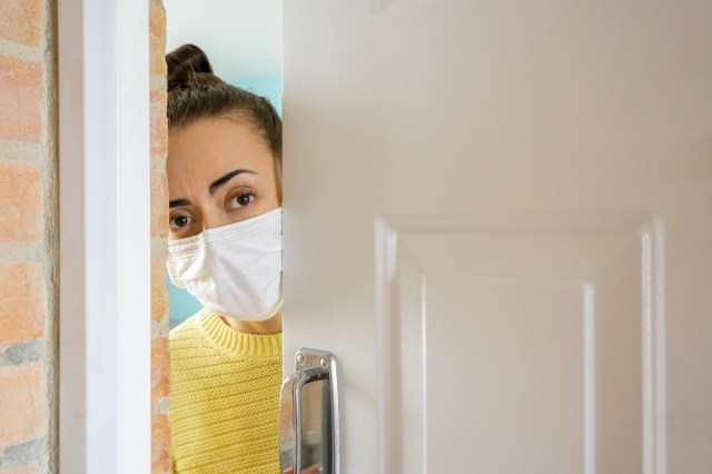 Woman at home opening the door wearing a facemask to avoid the coronavirus.