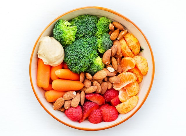 healthy snack bowl with broccoli carrots hummus almonds nuts strawberries fruit