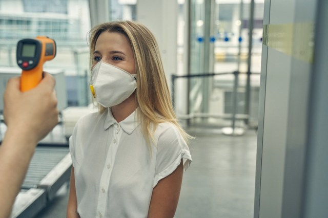 female wearing protective mask while standing opposite the worker of airport and checking temperature